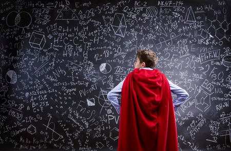 Young handsome school boy with red cape in front of big blackboard
