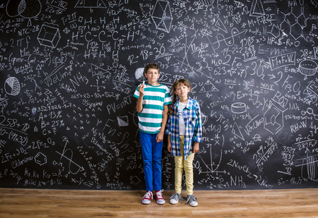 ni�os estudiando: Cute little boy and girl in front of a big blackboard. Studio shot on black background.