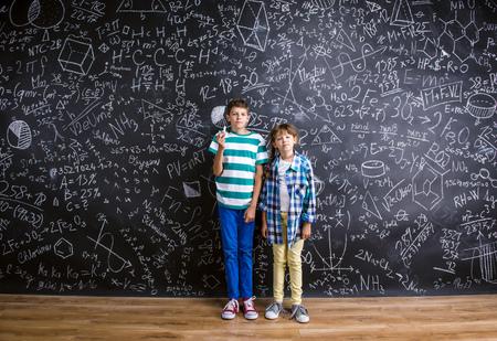 ni�o escuela: El ni�o peque�o lindo y muchacha delante de una pizarra grande. Foto de estudio sobre fondo negro. Foto de archivo