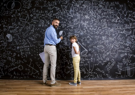 mentor: Young hipster school teacher with his pupil in front of big blackboard Stock Photo