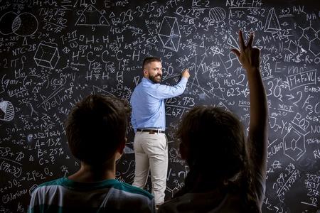 profesor alumno: Maestro de escuela en frente de la gran pizarra y sus estudiantes