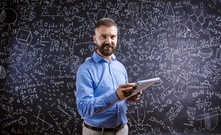 wise man: Young hipster school teacher in front of big blackboard
