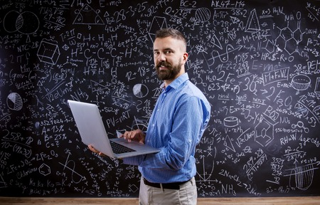 Young hipster school teacher in front of big blackboard
