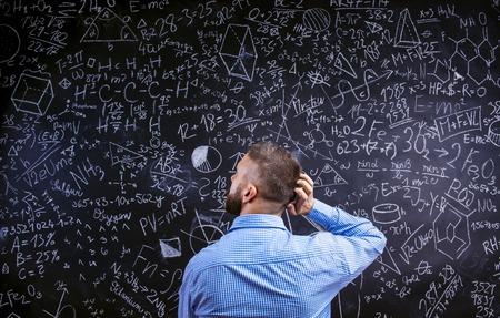 beard: Young hipster school teacher in front of big blackboard