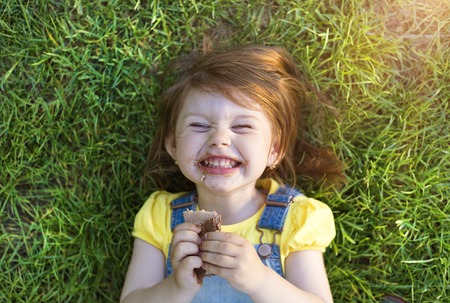 Cute little girl with chocolate face lying on a grass 스톡 콘텐츠