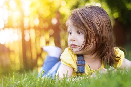 niños comiendo: Niña linda con la cara de chocolate acostado en una hierba Foto de archivo