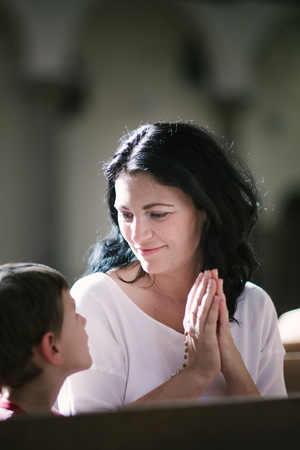 family praying: Beautiful woman with her son praying in the church Stock Photo