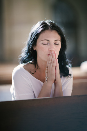 intercede: Beautiful woman with a rosary praying in the church Stock Photo