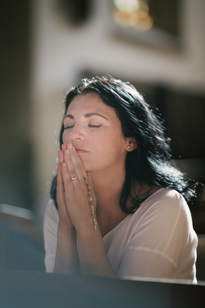 worship white: Beautiful woman with a rosary praying in the church Stock Photo