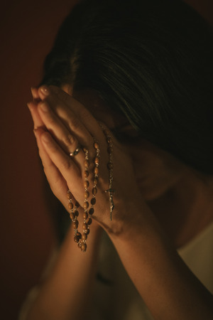 kneeling woman: Unrecognizable woman with a rosary praying in the church