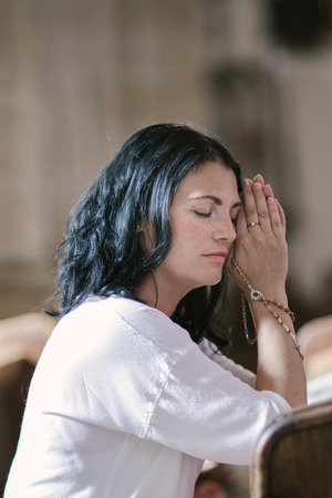 meditation help: Beautiful woman with a rosary praying in the church Stock Photo
