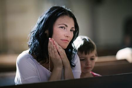familia en la iglesia: Hermosa mujer con su hijo rezando en la iglesia Foto de archivo