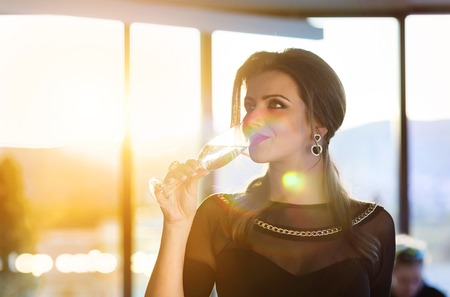 earings: Attractive young woman with a drink on a terrace of a bar Stock Photo