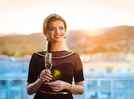 woman dress: Attractive young woman with a drink on a terrace of a bar Stock Photo
