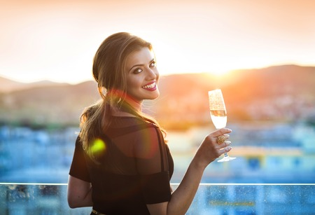 holding back: Attractive young woman with a drink on a terrace of a bar Stock Photo