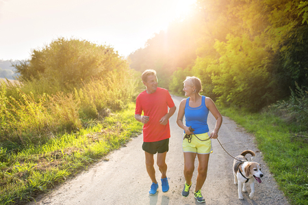 man relax: Active seniors running with their dog outside in green nature Stock Photo