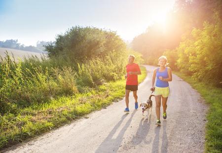 fitness hombres: Mayores activos que se ejecutan con su perro al aire libre en la naturaleza verde