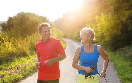 personas corriendo: Mayores activos que se ejecutan al aire libre en la naturaleza verde Foto de archivo