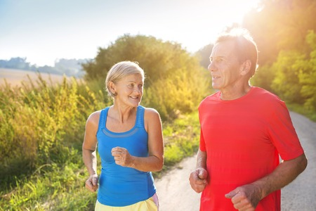 active woman: Active seniors running outside in green nature