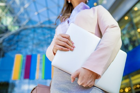 businesswoman suit: Attractive young business woman holding a notebook