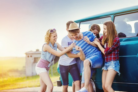 young man smiling: Young hipster friends on road trip on a summer day