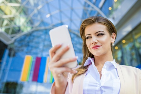 holding close: Attractive young business woman with smart phone