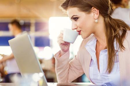 personas sentadas: Empresaria joven que trabaja en el cuaderno en caf� Foto de archivo