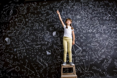 blackboard background: Cute little girl in front of big blackboard Stock Photo