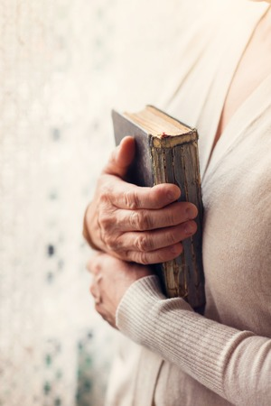 holy god: Unrecognizable woman holding a bible in her hands Stock Photo