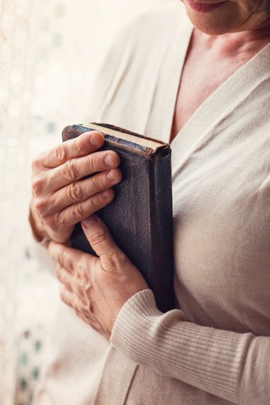 intercede: Unrecognizable woman holding a bible in her hands Stock Photo