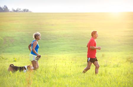 gente saludable: Mayores activos que se ejecutan con su perro al aire libre en la naturaleza verde