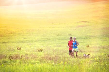 Actieve senioren lopen met hun hond buiten in de groene natuur