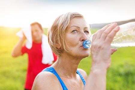 Actieve senioren die een onderbreking tijdens hun run buiten in de groene natuur