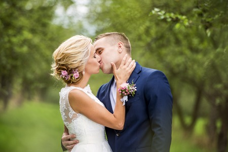 young couple kiss: Beautiful young wedding couple outside in nature Stock Photo