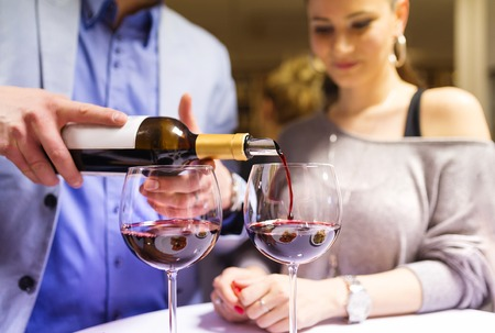 pouring wine: Beautiful young couple enjoying a drink in bar