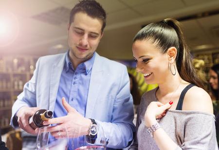 tomando vino: Hermosa joven pareja disfrutando de una copa en el bar Foto de archivo