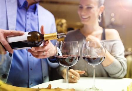 jovenes tomando alcohol: Hermosa joven pareja disfrutando de una copa en el bar Foto de archivo