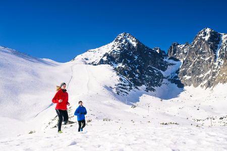 health and fitness: Young couple jogging outside in sunny winter mountains