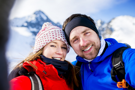two men: Young couple taking selfie on a hike outside in sunny winter mountains Stock Photo
