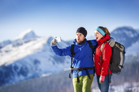 healthy sport: Young couple taking selfie on a hike outside in sunny winter mountains Stock Photo