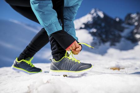 coureur: Jeune coureur attachant ses lacets ext�rieur en hiver la nature