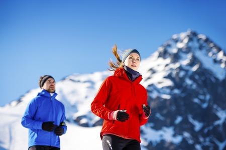 gente corriendo: Pareja joven que activa al aire libre en las montañas soleados de invierno
