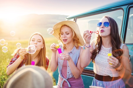 travel woman: Young hipster friends on road trip on a summer day