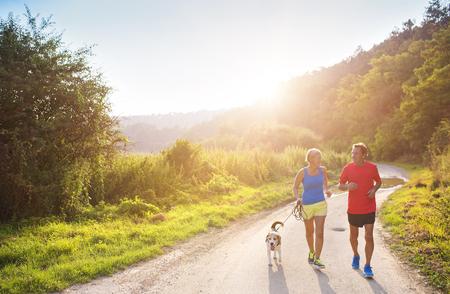 personas trotando: Mayores activos que se ejecutan con su perro al aire libre en la naturaleza verde