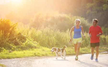 gente corriendo: Mayores activos que se ejecutan con su perro al aire libre en la naturaleza verde