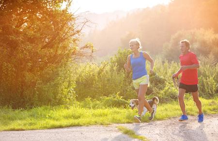 perro corriendo: Mayores activos que se ejecutan con su perro al aire libre en la naturaleza verde