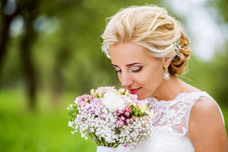 bouquet fleur: Belle jeune mariée en robe de mariée assis dans l'herbe