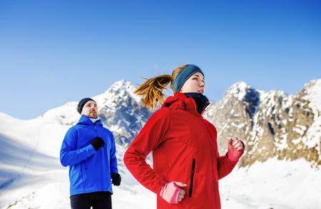 Jong koppel joggen buiten in zonnige winter bergen