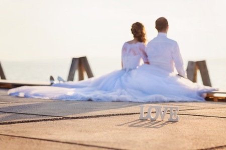 Beautiful young wedding couple sitting on the pier