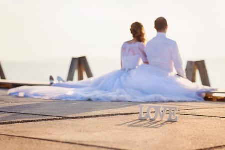 Mooie jonge bruidspaar zittend op de pier Stockfoto